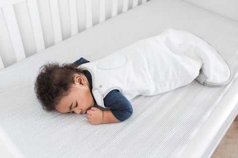 The baby sleeps on their belly in a crib.