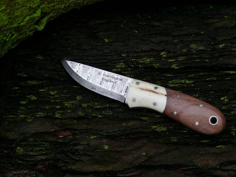 This necker measures 60mm in the blade (2.8mm thick) and over all length at 135mm. The blade steel is Odins Eye Damasteel with a 27 degree scandi grind.The Sambar Stag bolsters and stabilised apple-wood scales are held on with nickel silver pins and are complemented with a nickel silver thong tube. Presented in an oak tanned neck pouch.