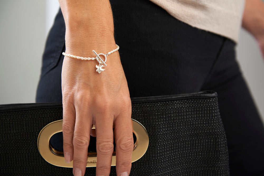 Vita cultured freshwater oval pearl bracelet with a silver swallow charm