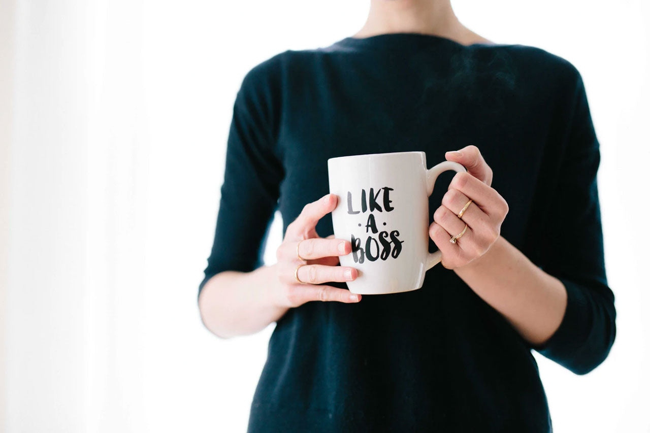 "A woman in a green sweater holds a ""Like a Boss"" coffee mug"