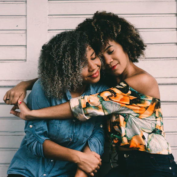 Two African American women hug one another in front of a white wall