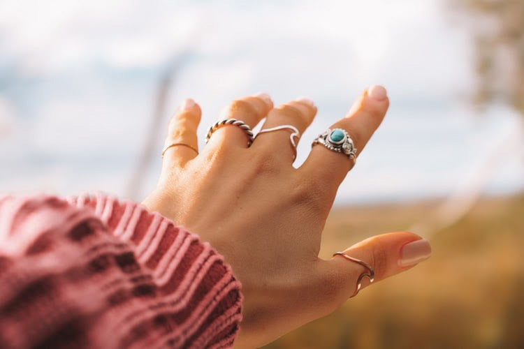 A woman's outstretched hand accessorized with a mix of rings.