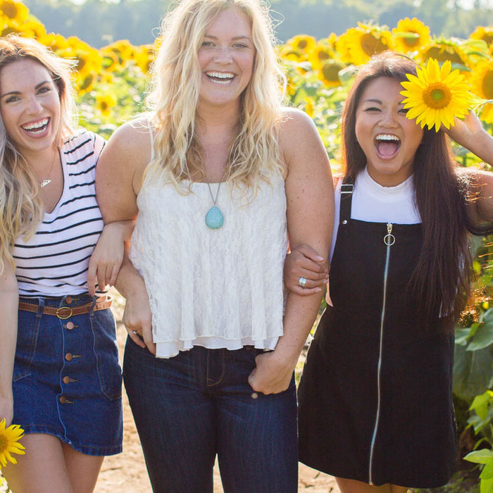Three women link arms as they walk through a sunflower field