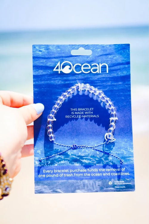 Woman holds blue, 4Ocean bracelet next to ocean water