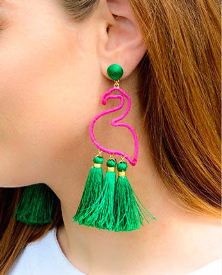 Woman wears bright pink, bold flamingo earrings as her summer accessory