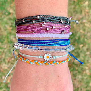 Woman wears a variety of stacked summer jewelry bracelets