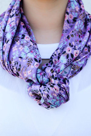 A woman models a purple, floral print scarf as an example of a spring work outfit idea