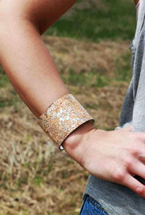 Woman models her sequined gold bracelet as part of her festival accessories