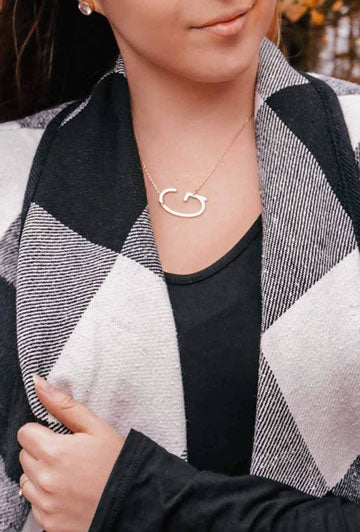 A woman models a gold 'G' monogram necklace