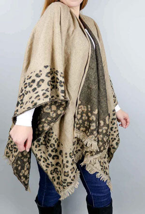 A woman models a brown, leopard print ruana as an example of a spring work outfit idea