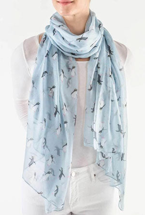 A woman models how to wear a spring scarf with a pastel-colored Penguin print scarf