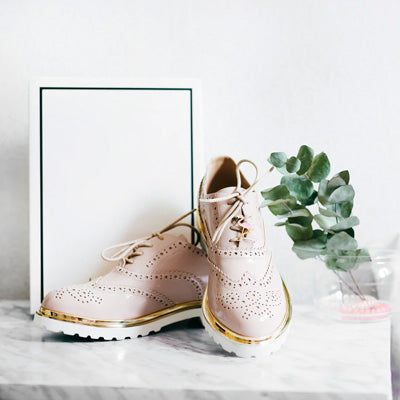 A pair of pale pink oxfords sit against a modern white background.