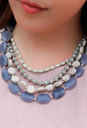 A woman models a purple, multi-layer stone necklace as an example of a spring work outfit idea