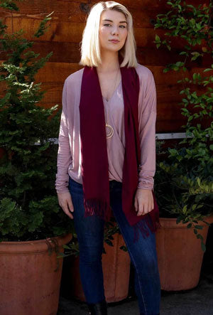 A woman models how to wear a spring scarf with a jeans and sweater ensemble