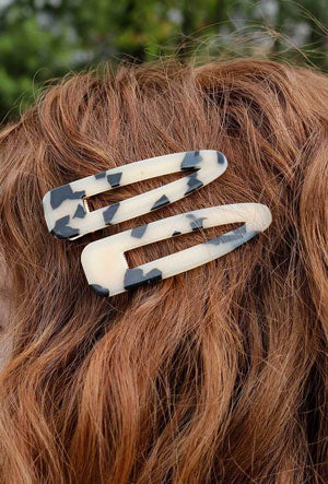 A woman models brown, tortoise-shelled inspired hair clips as an example of a spring work outfit idea