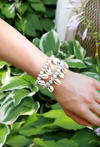 Woman models a cowry shell bracelet against a tropical background