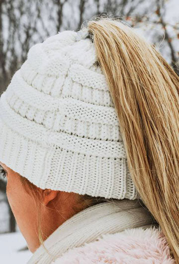 A woman sports a pony-tail beanie hat on a winter day