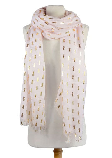 A white scarf decorated with a metallic pineapple print is modeled by a mannequin as an example of a trendy gift for women
