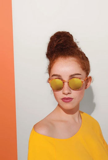 Woman models reflective yellow sunglasses against white wall