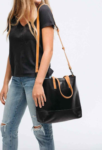Woman in jeans and t-shirt walks along with her black ABLE purse.