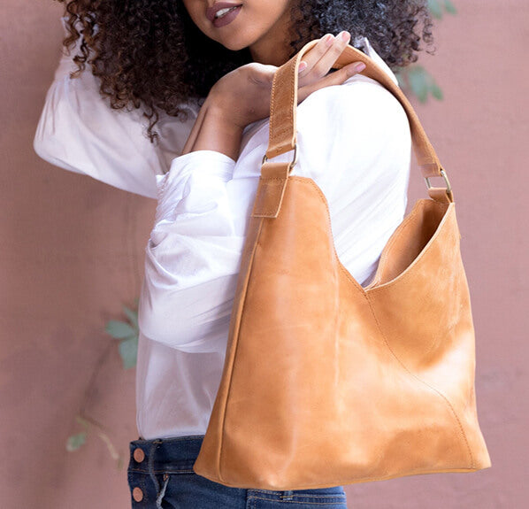 Model holds a brown, leather ABLE purse at her shoulder.