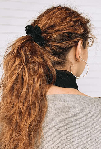 Woman with red hair pulled back in messy ponytail.