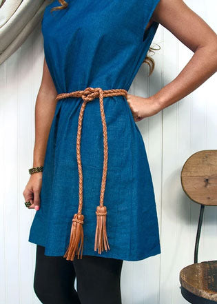 Woman wearing blue dress models cute back-to-school outfit with brown belt