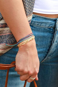 Woman wears a variety of colorful stacked summer jewelry bracelets