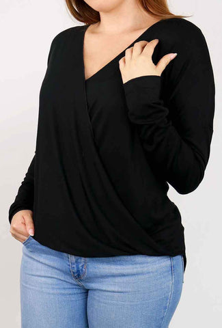 A woman models a cute fall look involving a black, crossover sweater top.