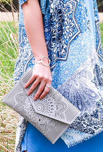 Woman poses with her laser cut, gray clutch summer accessories