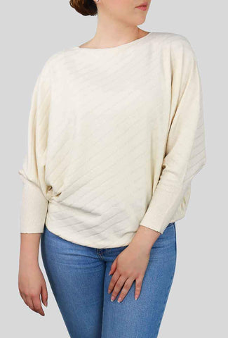 A woman models a cute fall look involving a white, dolman-sleeve sweater top.