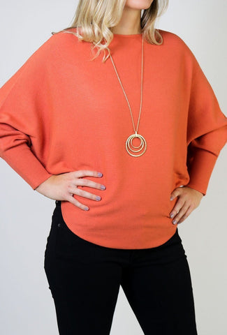 A woman models a cute fall look involving an orange, dolman-sleeve sweater top.