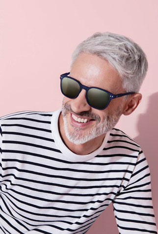 Man models his sunglasses as part of his festival accessories