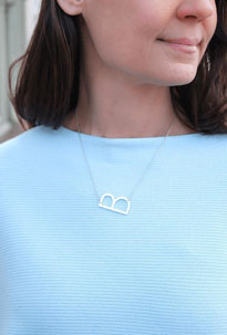 Woman wears dainty silver jewelry