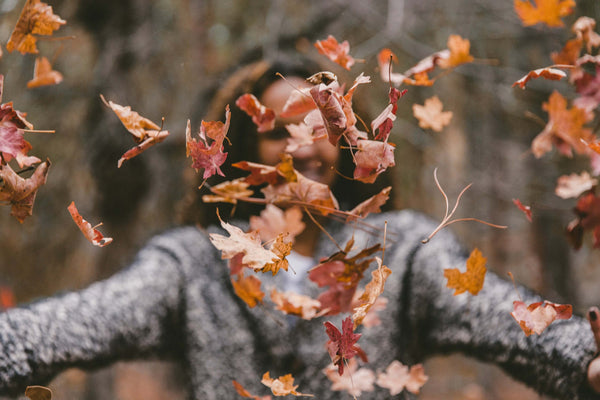 A woman tosses autumn leaves into the air.