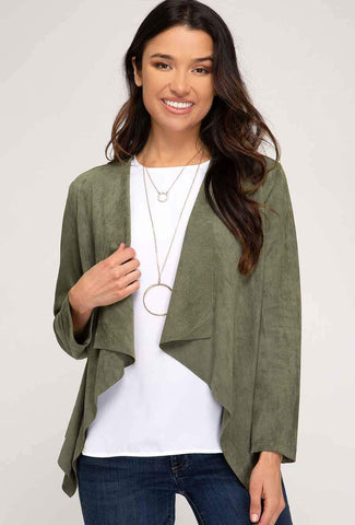 A woman models a cute fall look involving a green, vegan suede jacket.