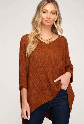 A woman models a cute fall look involving a burnt orange sweater.
