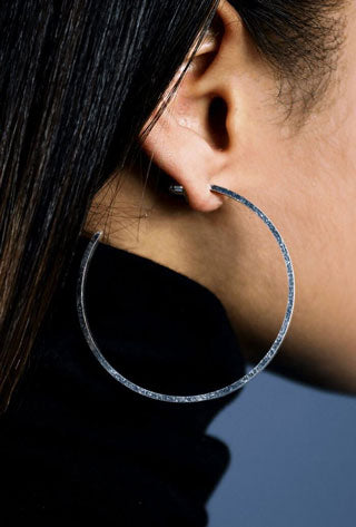 Woman models dainty silver jewelry hoop earrings