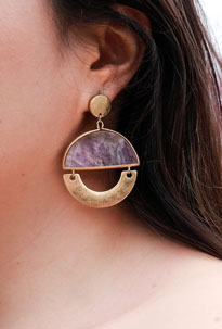 Woman models her stone purple earrings as part of her festival accessories