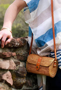 Woman models her straw purse as part of her festival accessories