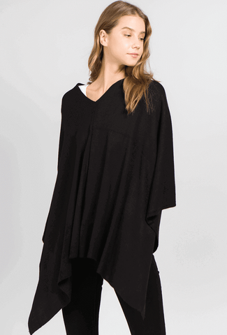 A woman models a cute fall look involving a black, travel poncho top.