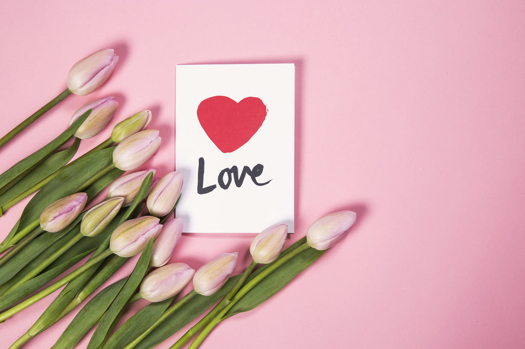 Valentine's Day Card with Pink Tulips Laying Beside It