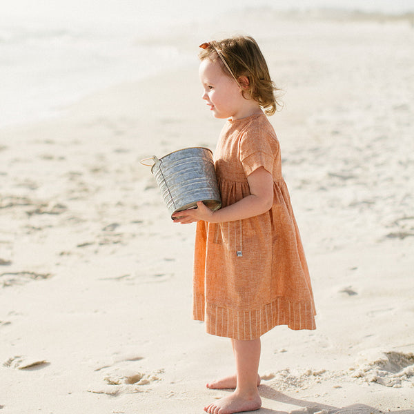 Baby Girl on Beach wearing Birdie Dress in Orange
