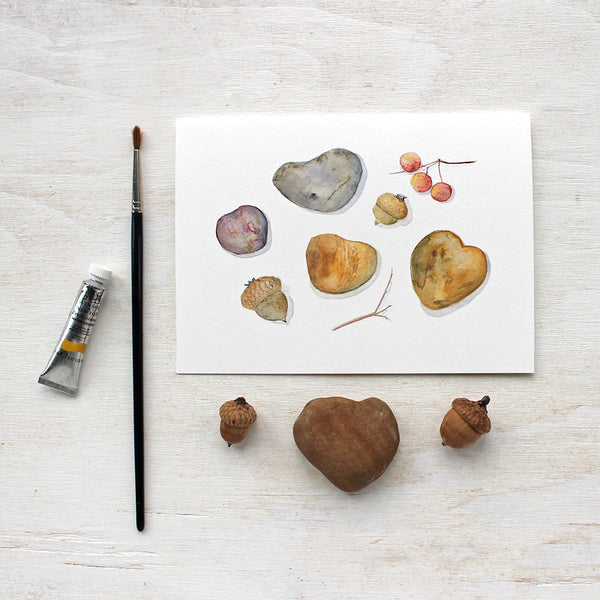 A lovely set of five note cards featuring a watercolor painting of heart-shaped stones, acorns and cranberries to create an autumn nature collection. Artist Kathleen Maunder