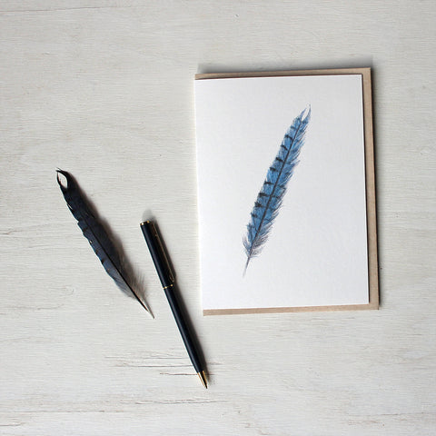 Note card featuring a watercolor painting of a blue jay feather. Artist Kathleen Maunder.