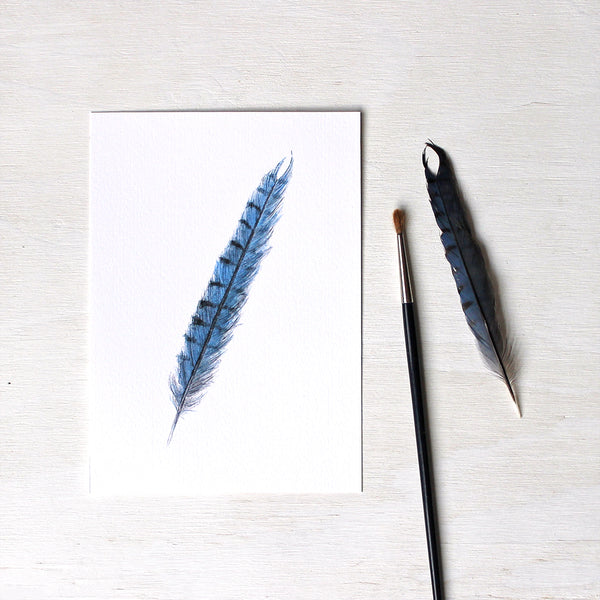 An art print featuring a watercolor painting of a blue jay feather. Artist Kathleen Maunder.