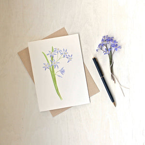 A note card featuring a watercolor painting of blue chionodoxa (glory of the snow) by artist Kathleen Maunder.