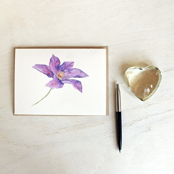Purple clematis flower watercolour painting on a note card. Artist Kathleen Maunder.