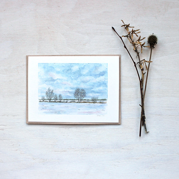 A note card featuring a watercolor painting of a winter landscape including a snowy field, trees and cloudy sky. Artist Kathleen Maunder.