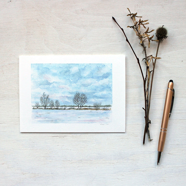 Note card featuring a watercolour painting of a snowy field, a line of trees and a cloudy sky. Artist Kathleen Maunder.